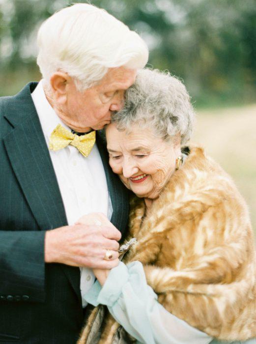 El novio besando a la novia en la cabeza.