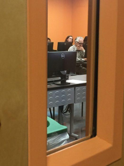 salon de clases con abuelo en computadora