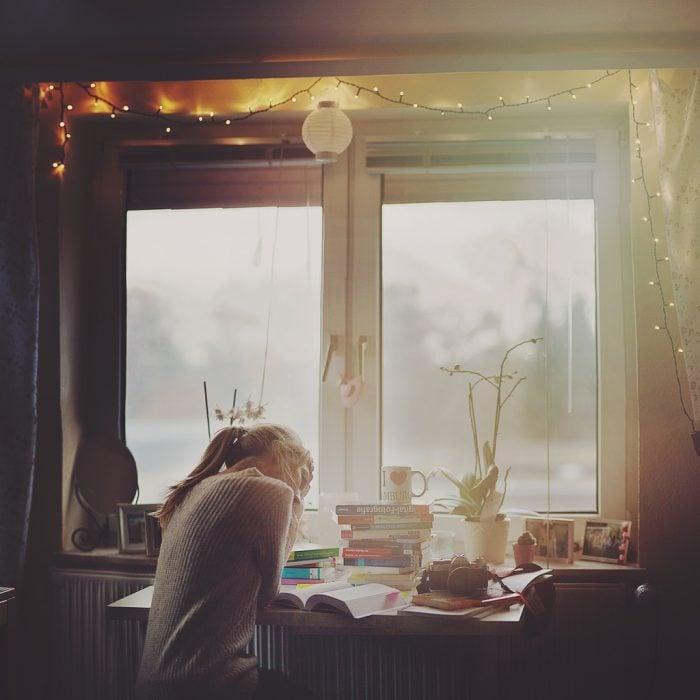 chica rubia estudiando en una mesa