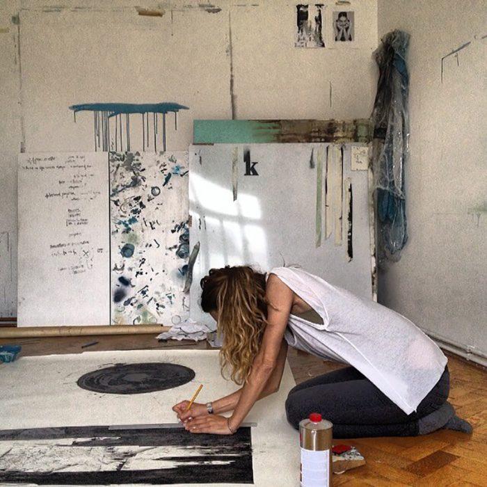 chica en el suelo con camisa blanca pintando