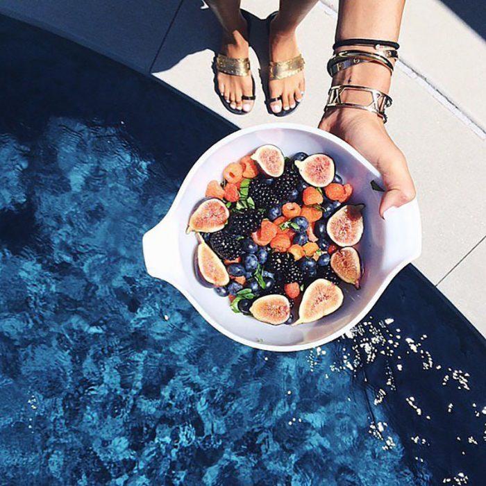 pies con manos y plato de frutas sobre alberca