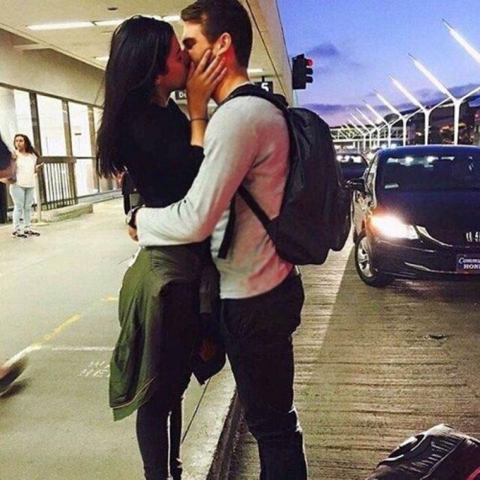pareja abrazada con gorra en aeropuerto