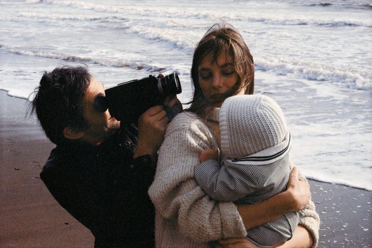 hombre grabando a su mujer cargando un bebé en la playa