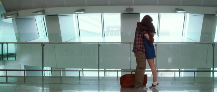 pareja abrazada con una maleta en aeropuerto