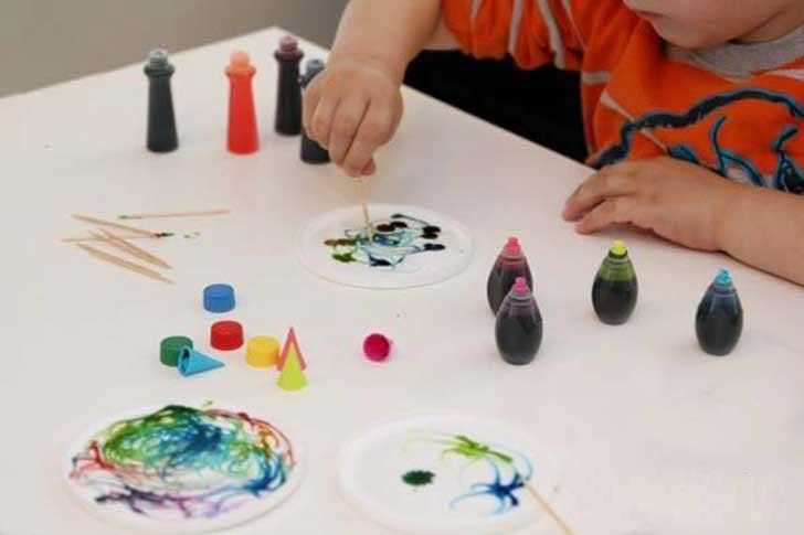 Niños pintando con palillos y pintura vegetal.