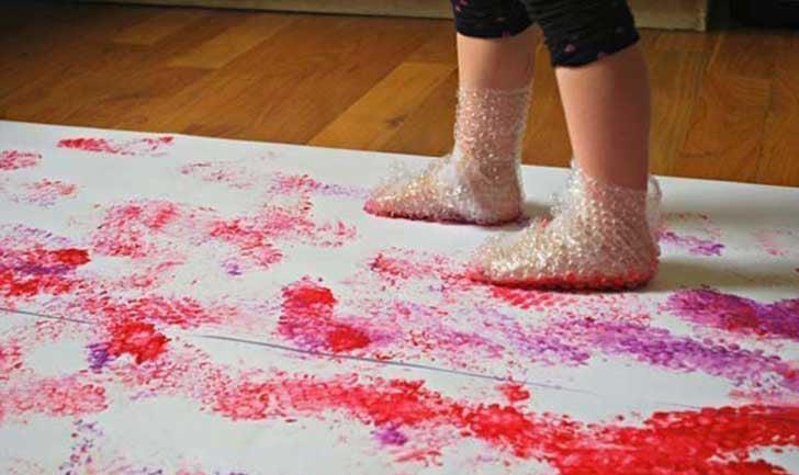 Niña pintando con zapatos hecho con plástico de bolitas.