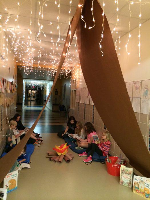 Niños leyendo en un campamento de papel.