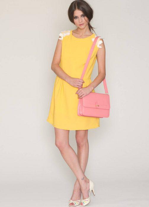 Mujer con vestido amarillo y bolsa rosa.