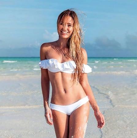 Chica en la playa usando flamenkini blanco.