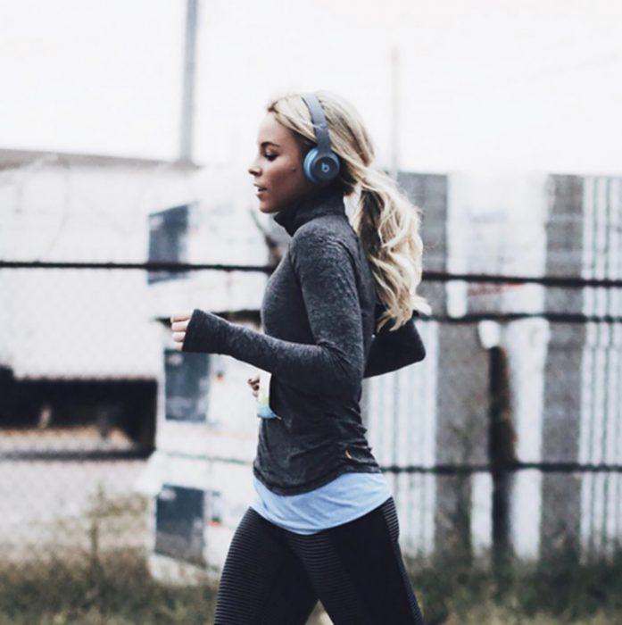 mujer rubia corriendo con audifonos