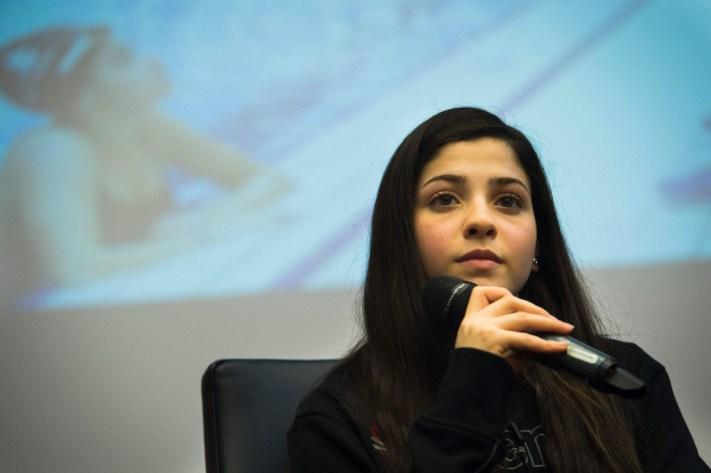 chica blanca con cabello largo sentada con microfono en mano