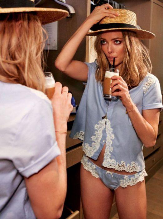 chica probándose un sombrero viéndose en el espejo
