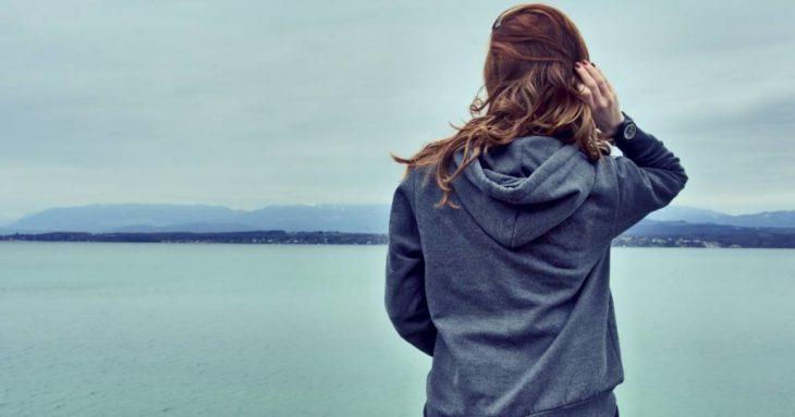 chica mirando hacia el lago