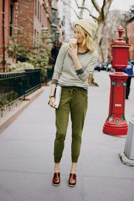 mujer rubia pantalon verde y gorro