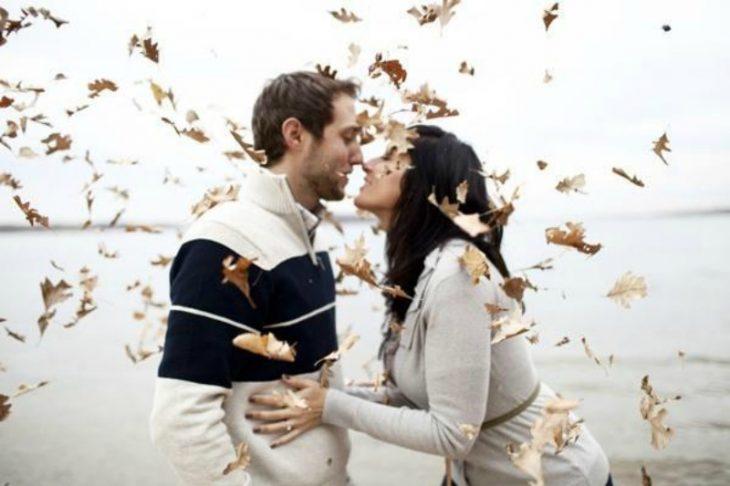 pareja se da besos entre hojas de otoño