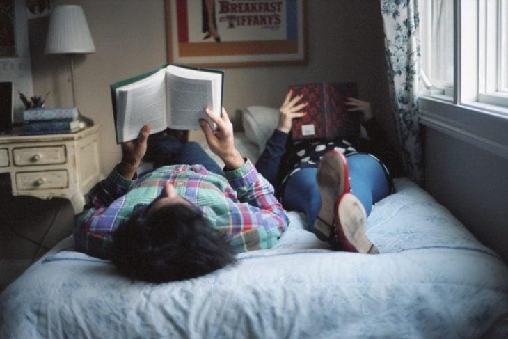 pareja acostada en la cama leyendo