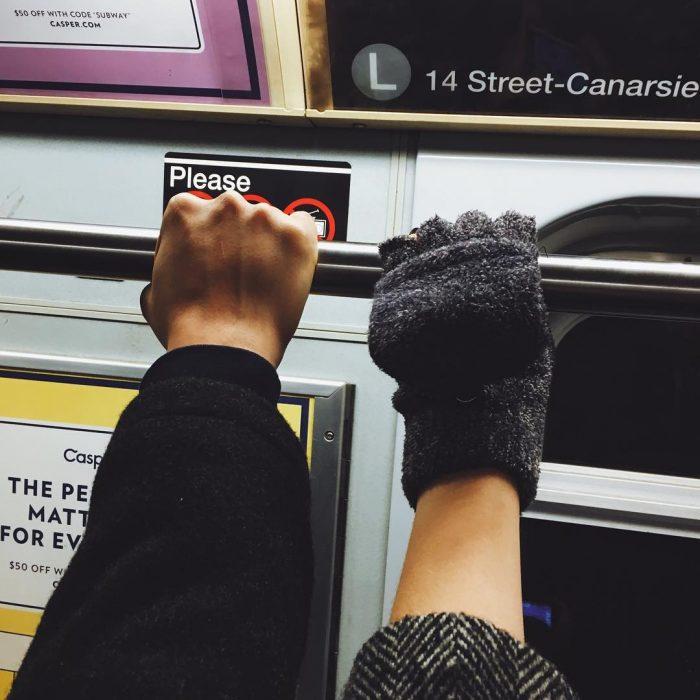Dos personas agarradas del tubo del metro.