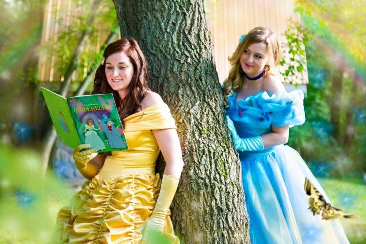 mujers vestidas de princesas con libro de cuentos