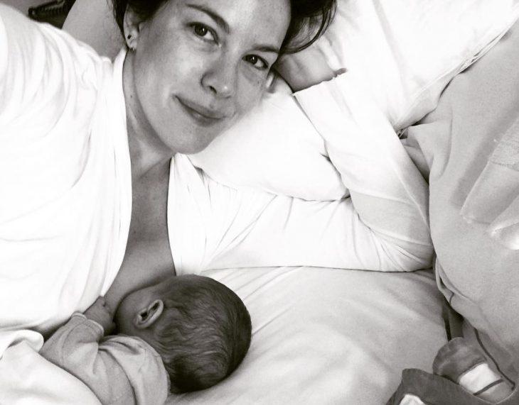 mujer blanca amamantando a bebe en la cama