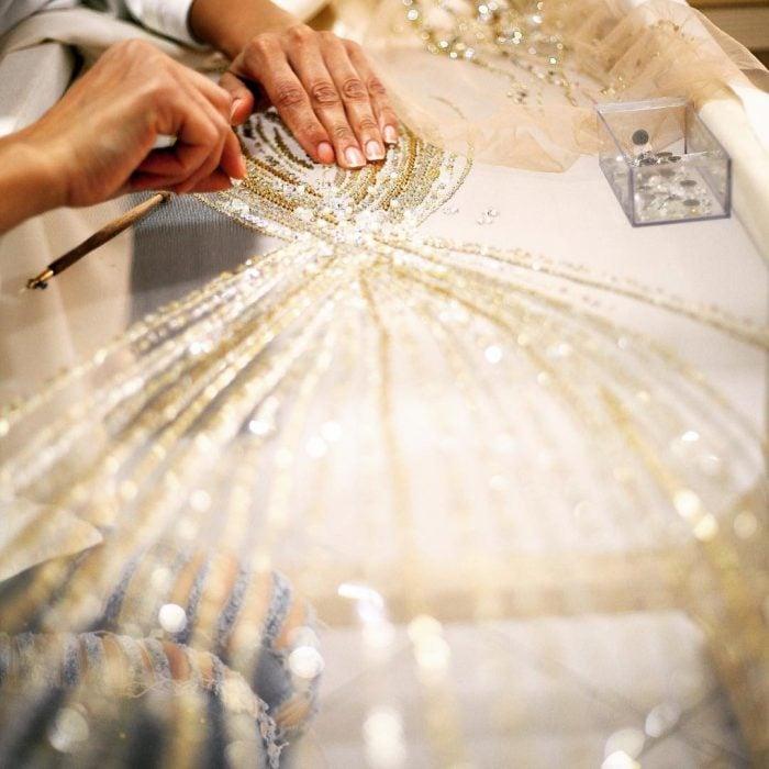 manos bordando tela de vestido de novia