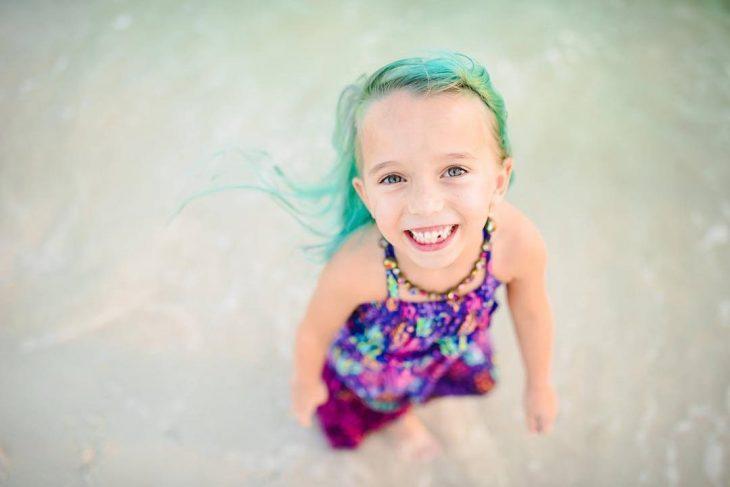 La niña sonriendo a la cámara.
