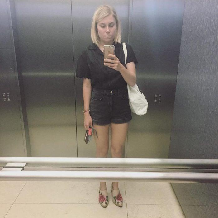 Chica se toma selfie en un elevador.