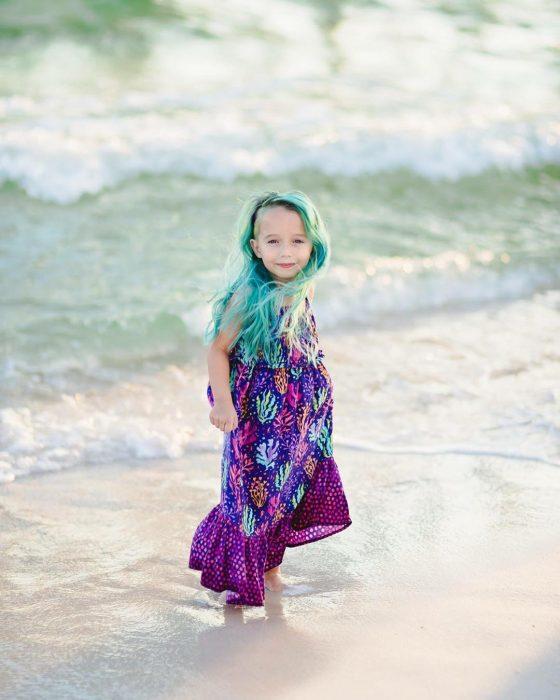La niña en la playa luciendo su look.