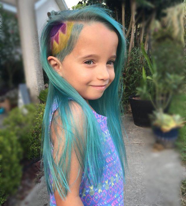La niña luciendo la mitad de su cabeza rapada.
