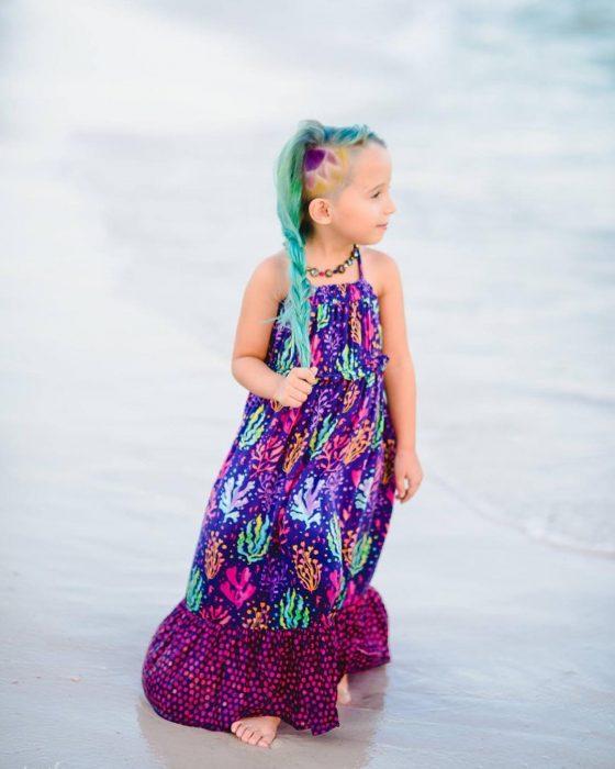 La niña luciendo su look mientras camina por la playa.