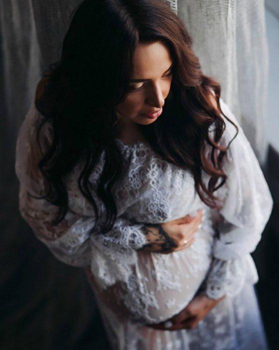 mujer embarazada con vestido blanco triste