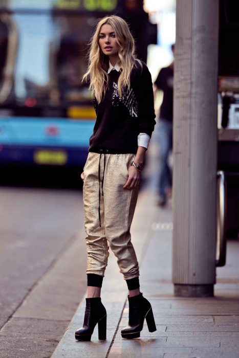 mujer pantalon dorado y sueter negro