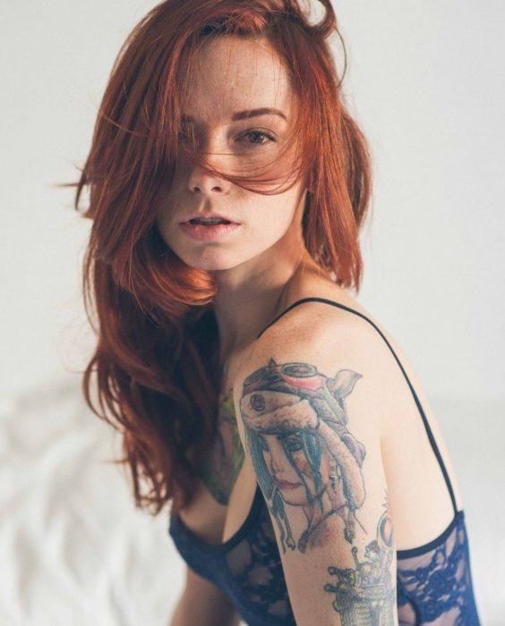 mujer pelirroja con tatuajes