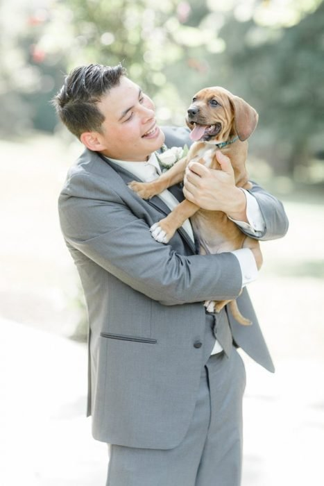 Groom carrying one of the puppies.