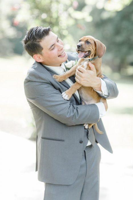 El novio cargando a uno de los perritos.