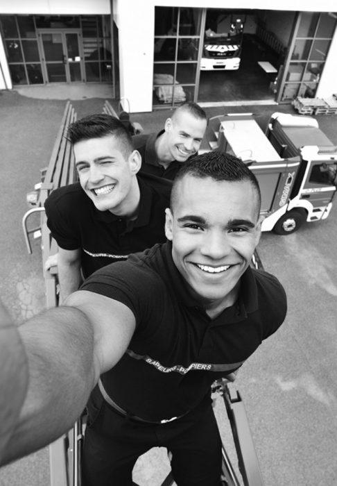 hombres sonriendo se toman selfie