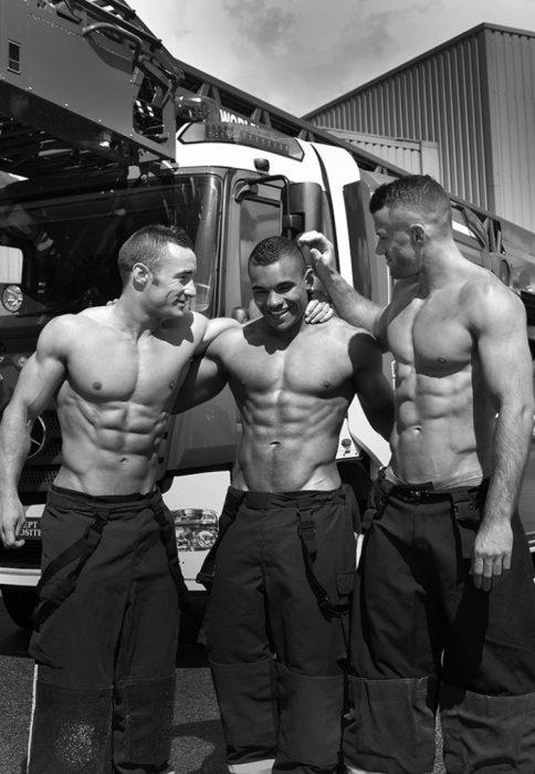 tres hombres sin camisa se abrazan y sonríen