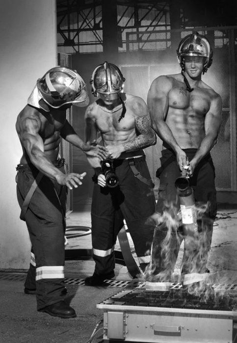 hombres bomberos sin camisa apagan fuego