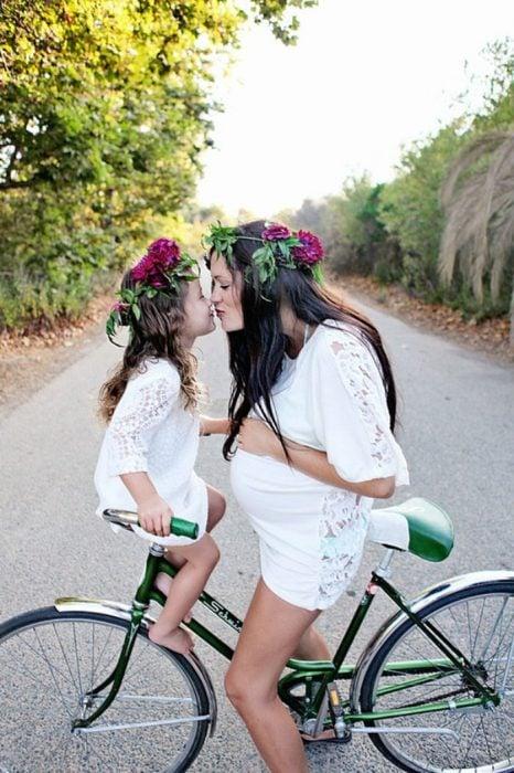 madre e hija con flores en la cabeza en una bicicleta