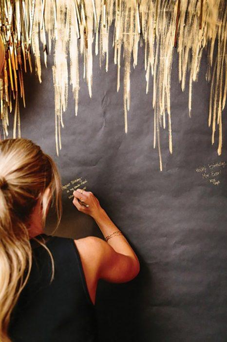 pared negra con rayada de dorado y mujer rubia escribiendo