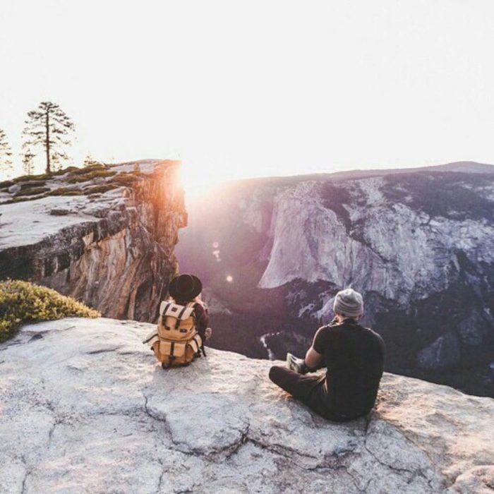 Pareja observando el amanecer en una montaña