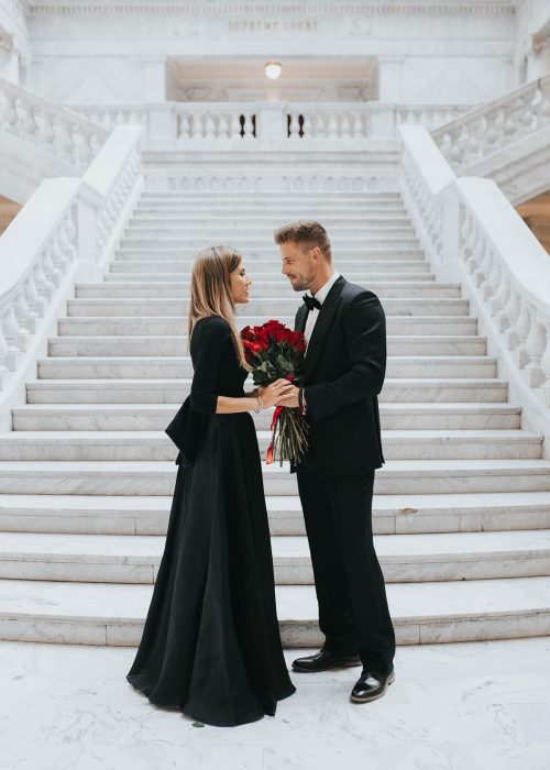 Novio regalando flores a su novia mientras están al final de las escaleras