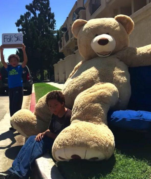 Niños vendiendo oso gigante