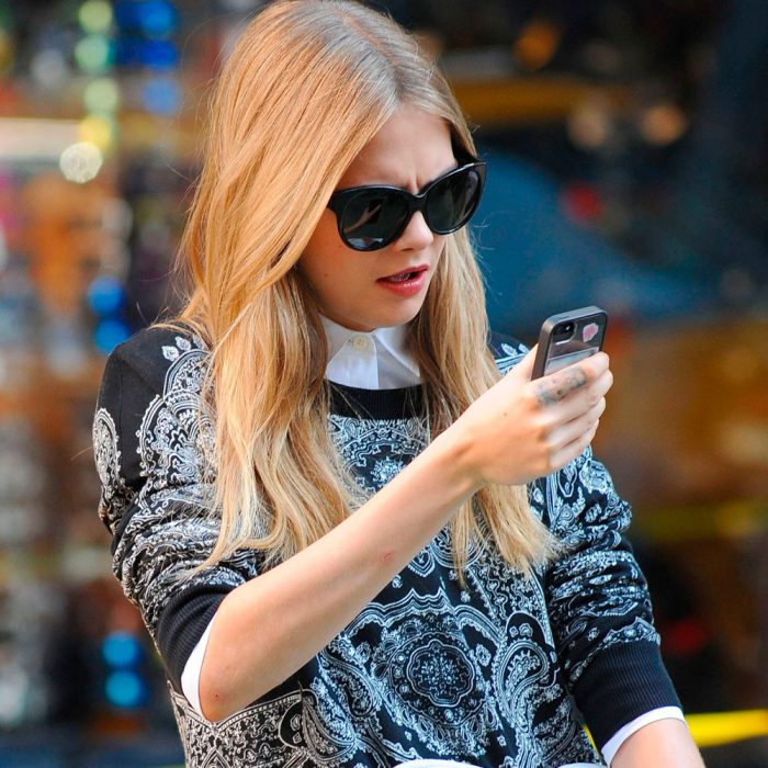 mujer rubia con lentes mirando su celular