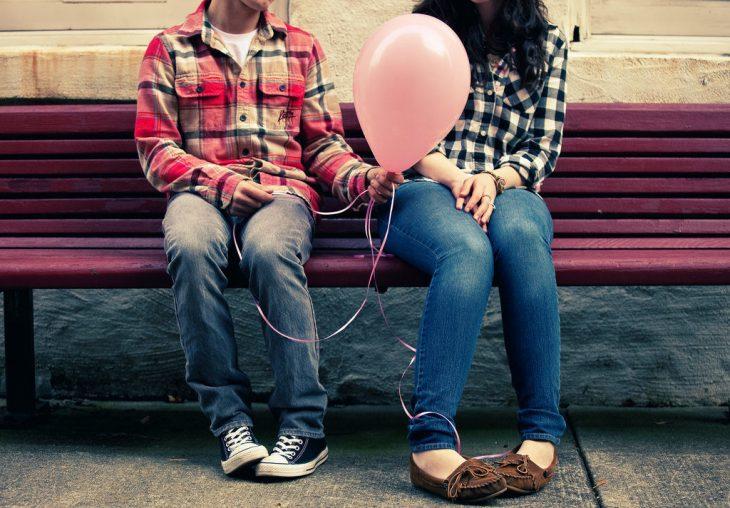 pareja sentada en una banca con un globo