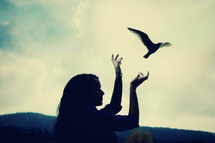 chica a contraluz deja volar a un ave