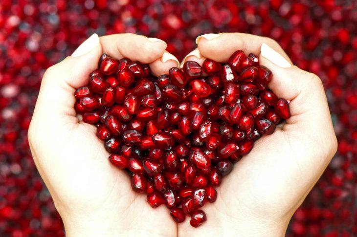 manos en forma de corazón con semillas de granada