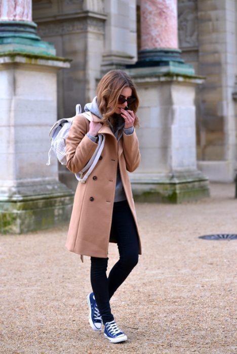 mujer con abrigo cafe y tenis converse