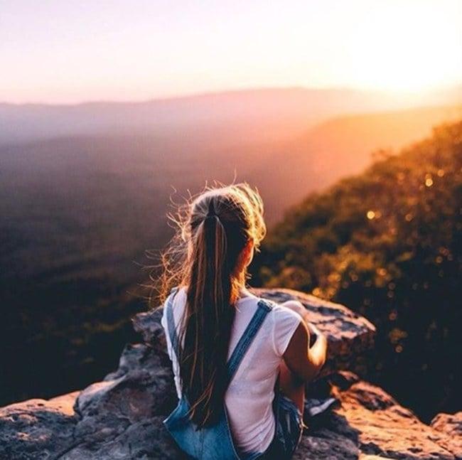 Chica observando el amanecer en una montaña