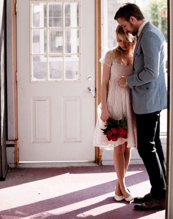 Chica rubia abrazada de hombre y ramo de flores