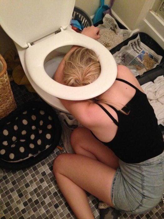 mujer rubia en con resaca en el inodoro
